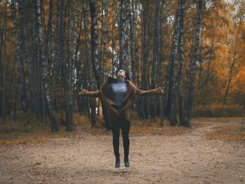 photo of woman in autumn forest jumpinh