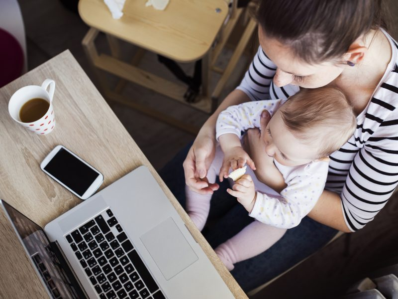 photo of mom in need of adrenal support foods - holding baby while working on laptop