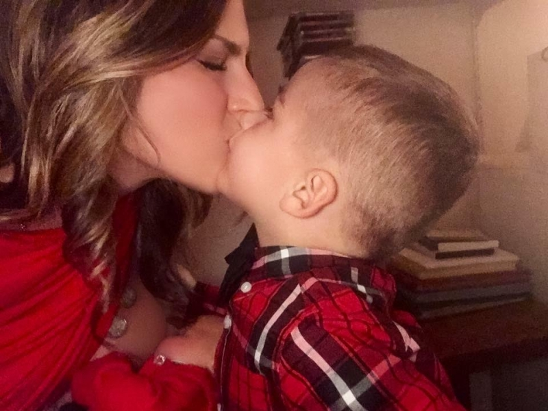 Photo of Kimberly Spair breastfeeding daughter and giving son a kiss