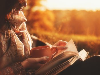 photo of woman drinking tea and reading outside for self-care