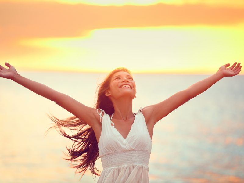 photo of happy woman with her arms up embracing the truth and autoimmune healing