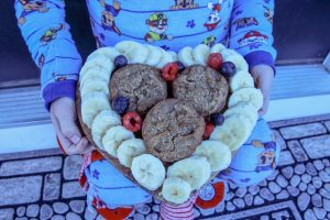 photo of Kim's son holding banana muffins plated with bananas in heart shape
