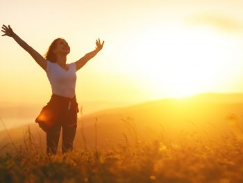 Photo of woman with arms raised in triumph in field at sunset