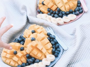 photo of fruit plates with melon, blueberries, and bananas
