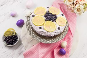 photo of spiced lemon cake with wild blueberry frosting, overhead view with Easter eggs