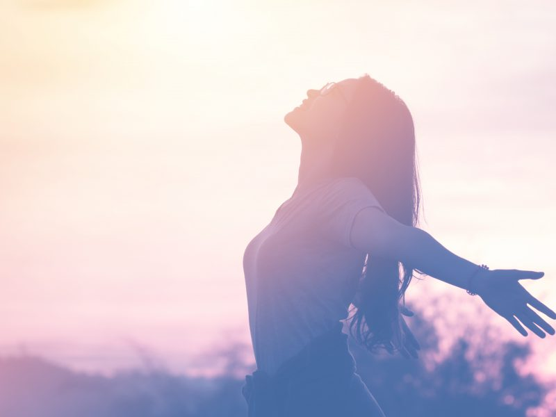 photo of young carefree woman with arms outstretched in summer sunset sky