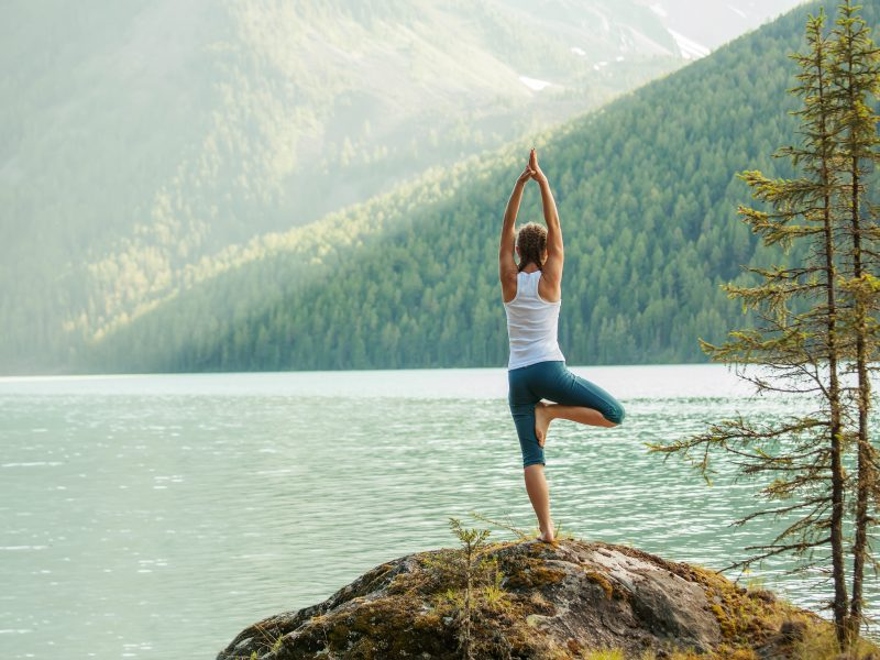 photo of young woman doing yoga in front of lake with mountains in background