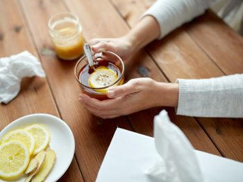 photo of a woman holding a mug of hot tea with lemon, cold and flu home remedies