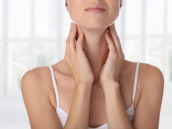 photo of woman holding her thyroid gland