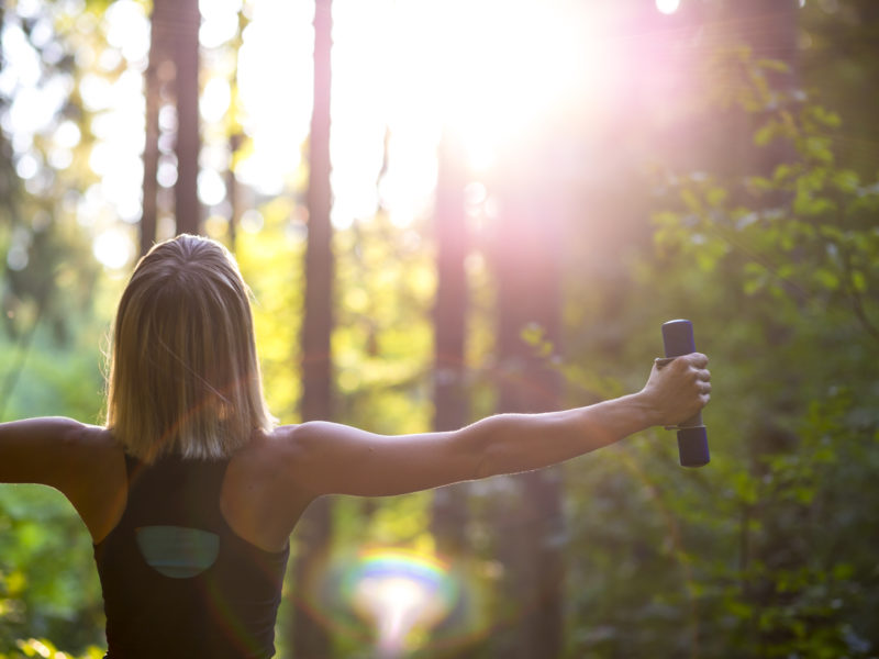 photo of woman lifting dumbbells out in nature
