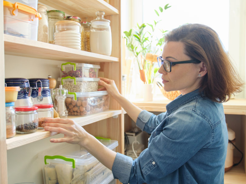 photo of woman looking through her pantry