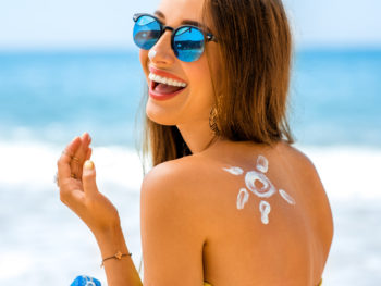 photo of happy woman on beach with sunscreen on her back