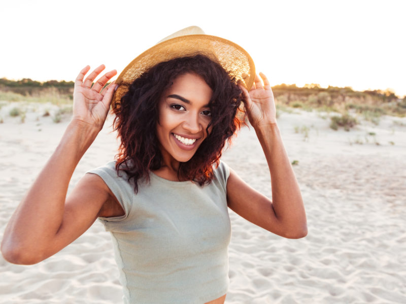 photo of young woman wearing hat on the beach