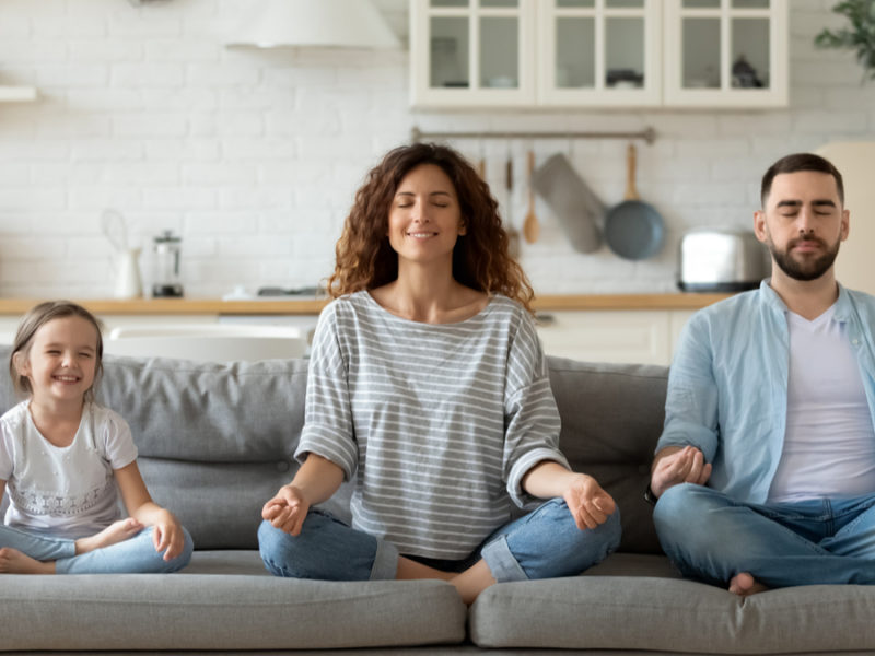 mom, dad, and daughter doing yoga on the couch