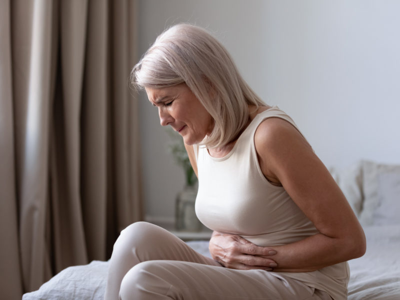 photo of woman sitting on bed in discomfort
