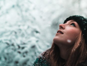 photo of woman looking up at snow