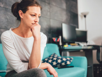 woman with anxiety sitting on couch with hand on face