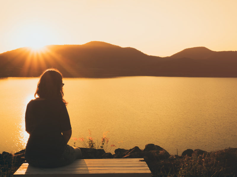 photo of the silhouette of woman sitting alone on a dock at sunset